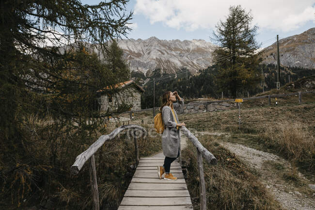 Switzerland, Engadin, woman on a hiking trip on a wooden bridge — Stock Photo
