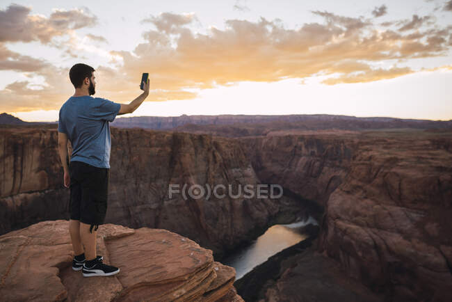 EUA, Arizona, Colorado River, Horseshoe Bend, jovem no miradouro usando smartphone, fotografando — Fotografia de Stock