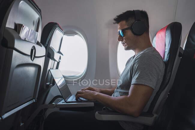 Man in airplane, using laptop, headphones — Stock Photo