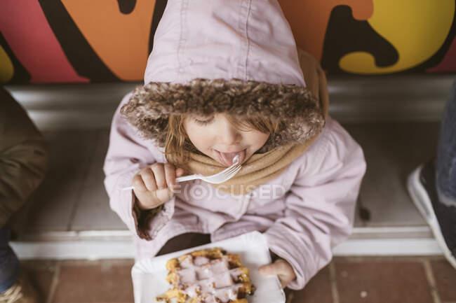 Belgio, bambina che mangia la cialda belga in inverno all'aperto — Foto stock