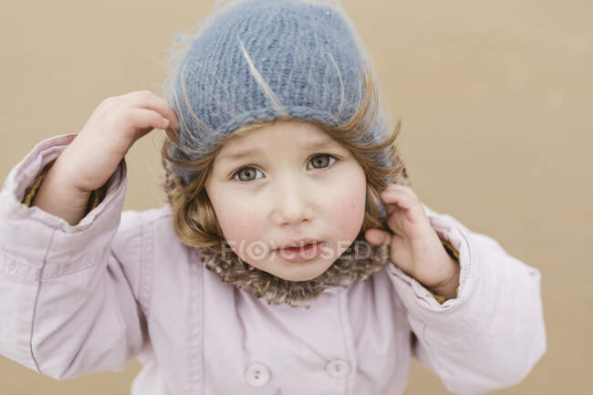 Portrait of unhappy little girl on the beach in winter — Stock Photo
