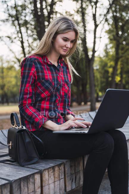 Модная молодая женщина, сидящая на лавочке и работающая на ноутбуке — стоковое фото
