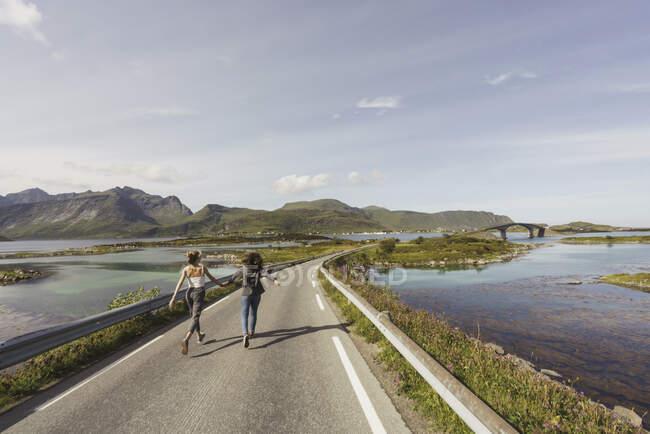 Молодые женщины, идущие по пустой дороге, Оланд, Норвегия — стоковое фото