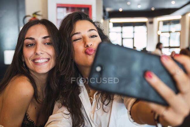 Портрет двух друзей, делающих селфи со смартфоном в кофейне весело — стоковое фото