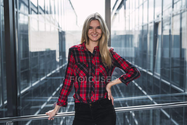 Portrait of smiling young woman wearing plaid shirt — Stock Photo