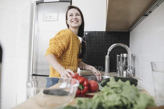 Портрет счастливой молодой женщины, готовящей салат на современной кухне — стоковое фото