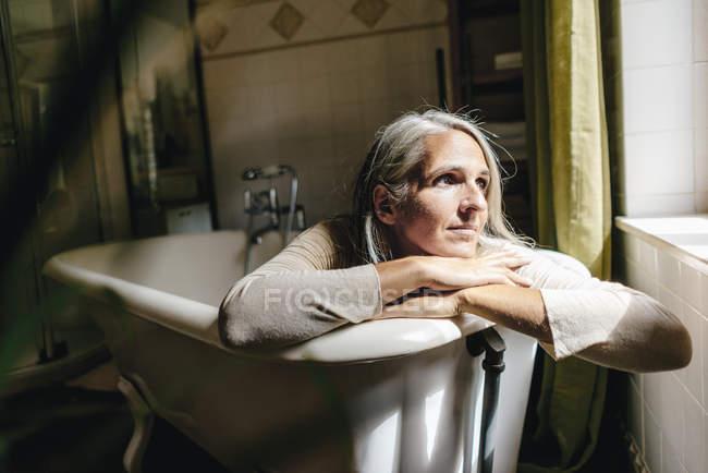 Портрет печальной женщины, сидящей в ванной — стоковое фото