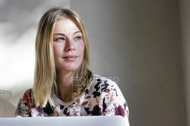 Retrato de mujer rubia con portátil en un café mirando a la distancia - foto de stock