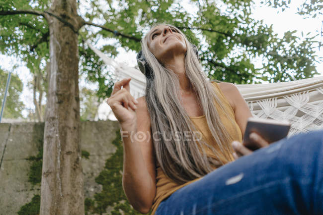 Woman with cell phone sitting in the garden listening music with headphones — Stock Photo