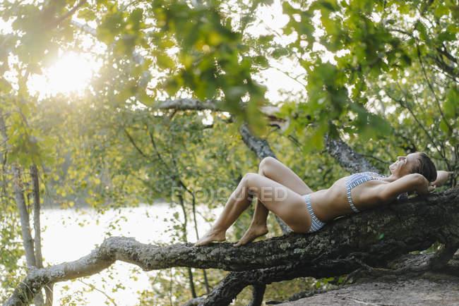 Mulher relaxada vestindo um biquíni e deitada em um tronco de árvore em um lago — Fotografia de Stock