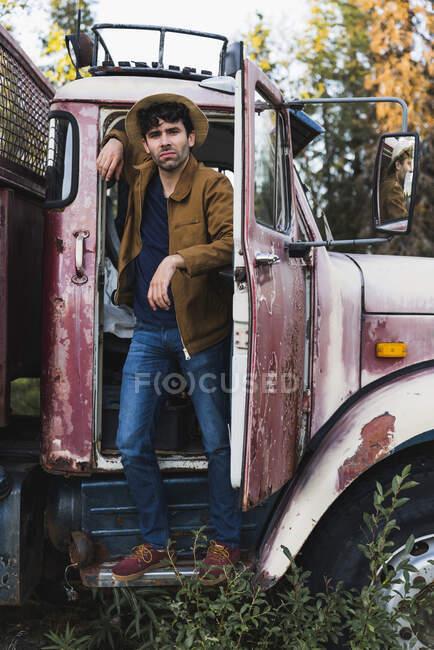 Крутий молодий чоловік стоїть у хижці розбитого вантажного автомобіля. — стокове фото