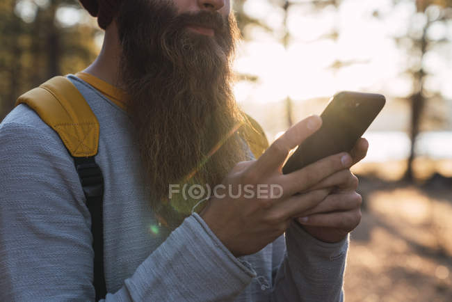 Close-up of bearded man using cell phone on a hiking trip in a forest — Stock Photo