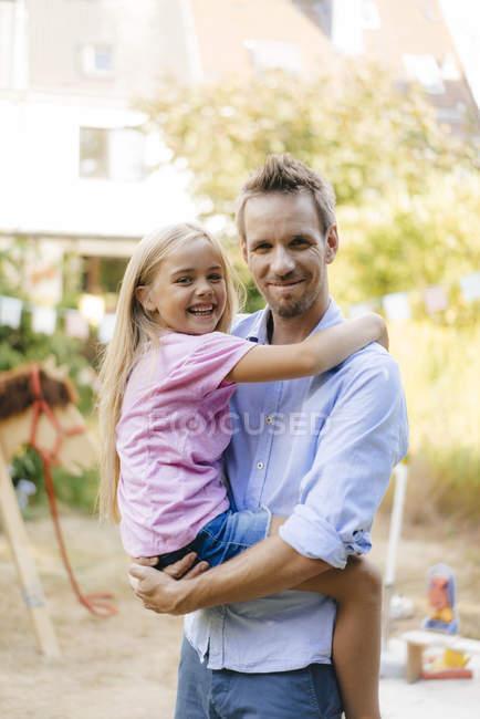 Портрет усміхнений батько, що несе дочку в саду — стокове фото