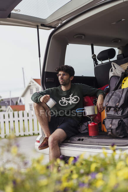 Молодий чоловік сидить у кемпінгу, готуючи каву на пічці для кемпінгу. — стокове фото