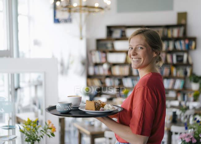 Портрет усміхаючої молодої жінки, яка обслуговує каву і тістечка в кафе — стокове фото