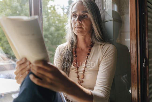 Retrato de la mujer sentada en el alféizar de la ventana en casa y leyendo un libro - foto de stock