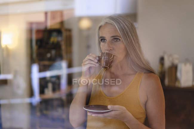Портрет деловой женщины, пьющей чашку кофе в своем магазине — стоковое фото