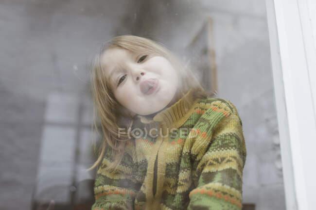 Ritratto di bambina attaccare la lingua mentre si guarda fuori dalla finestra — Foto stock