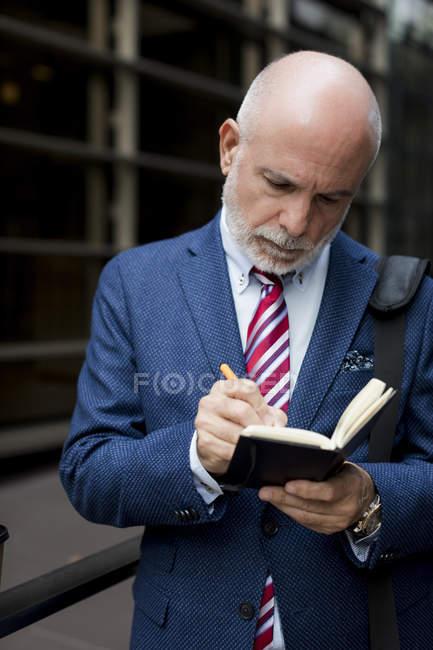 Senior businessman writing in diary outdoors — Stock Photo