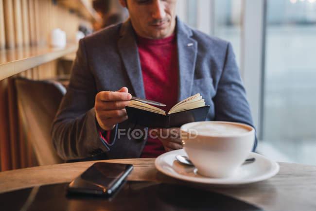 Бізнесмен сидячи в ресторані пити каву і перевіряти його ноутбук — стокове фото