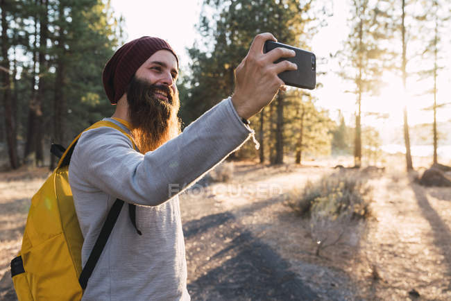 USA, North California, smiling bearded man taking a selfie in a forest near Lassen Volcanic National Park — Stock Photo