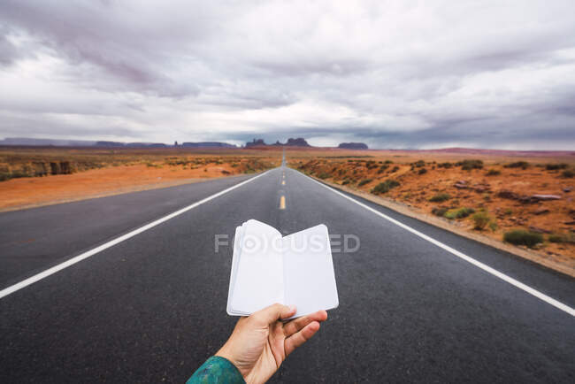USA, Utah, Hand holding blank notebook over road to Monument Valley — Stock Photo