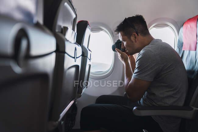 Человек, фотографирующийся в самолете — стоковое фото