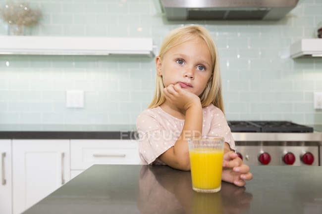 Portrait of pensive girl in kitchen with glass of orange juice — Stock Photo