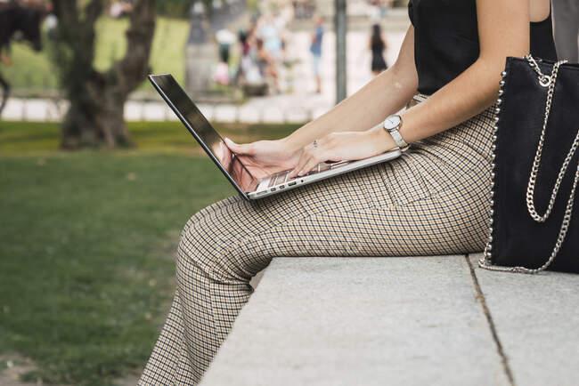 Junge Frau sitzt im Freien mit Laptop an einer Wand, Teilsicht — Stockfoto