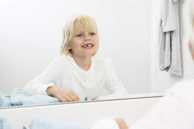 Lächelnder Junge mit Zahnlücke blickt in Badezimmerspiegel — Stockfoto