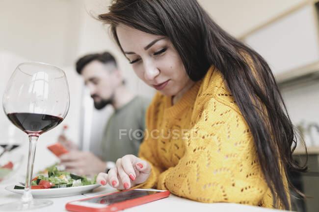 Молодая женщина проверяет смартфон за обедом дома — стоковое фото