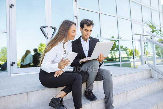 Businesswoman and businessman working with tablet and laptop outside office building — Stock Photo