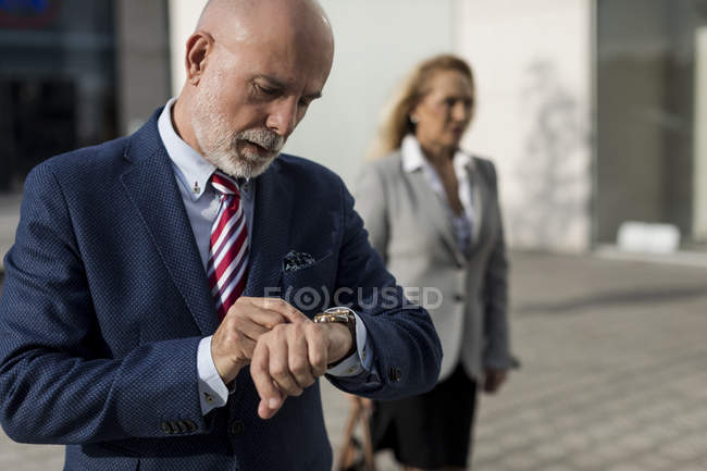 Senior businessman checking the time with businesswoman in background — Stock Photo