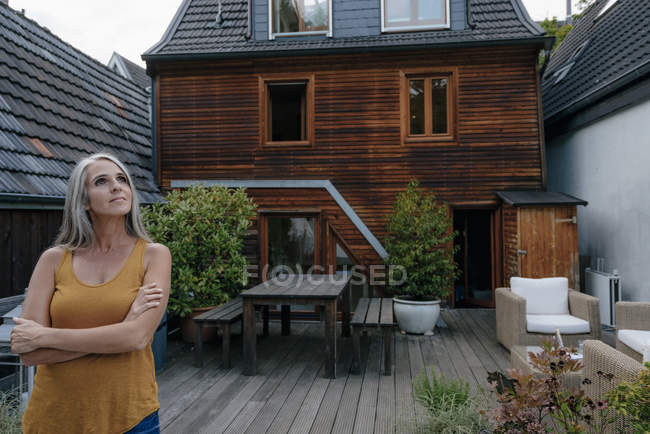 Woman standing on terrace of her house and enjoying tranquility — Stock Photo