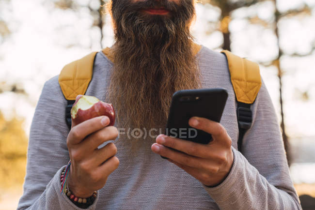 Close-up of bearded man using cell phone and eating an apple on a hiking trip in a forest — Photo de stock
