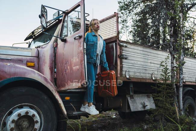 Молодая женщина позирует у разбитого винтажного грузовика, держа в руках канистру с бензином — стоковое фото