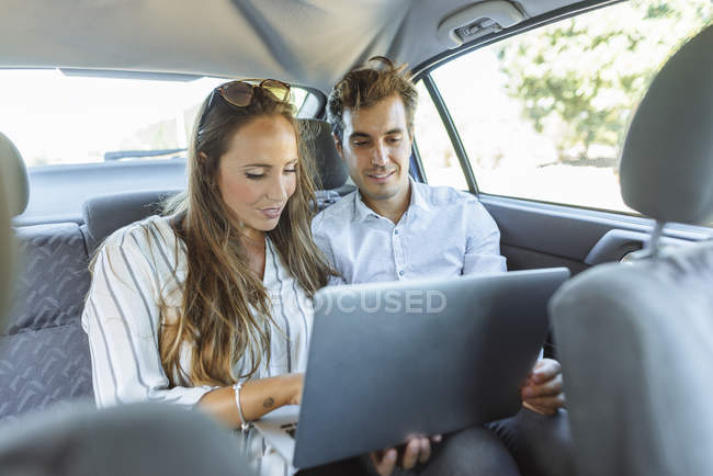 Couple using laptop on back seat of a car — Stock Photo