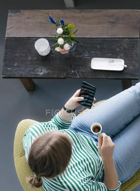 Vue aérienne de la jeune femme avec téléphone portable et expresso dans un café — Photo de stock