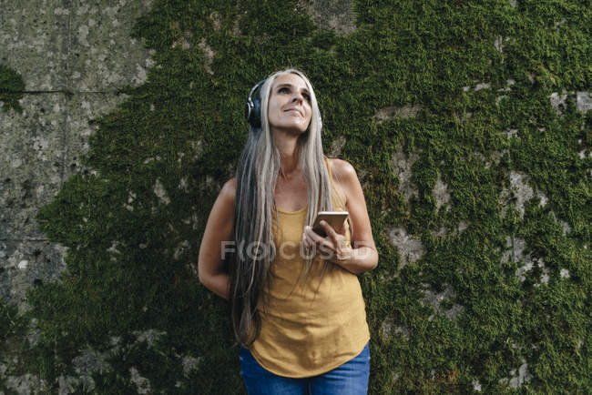 Woman with cell phone standing in front of wall listening music with headphones — Stock Photo