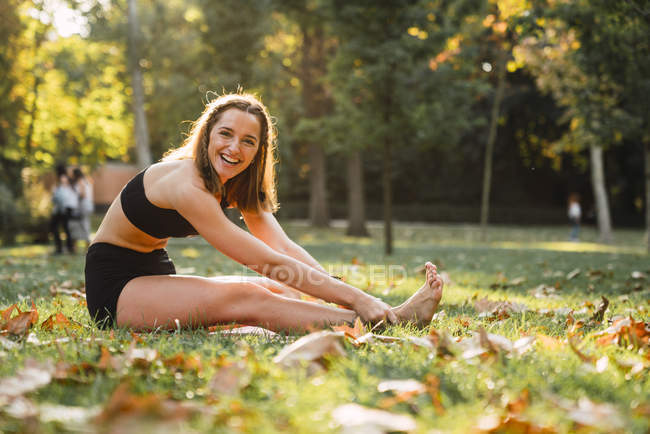 Fit young woman practicing yoga in a park — Stock Photo