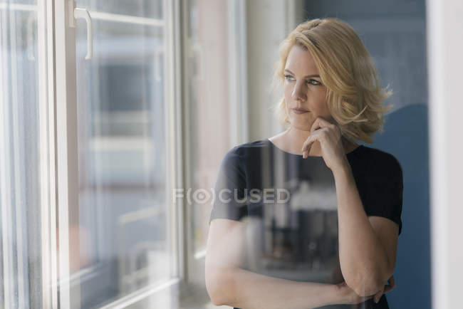 Serious blond woman looking out of window — Stock Photo