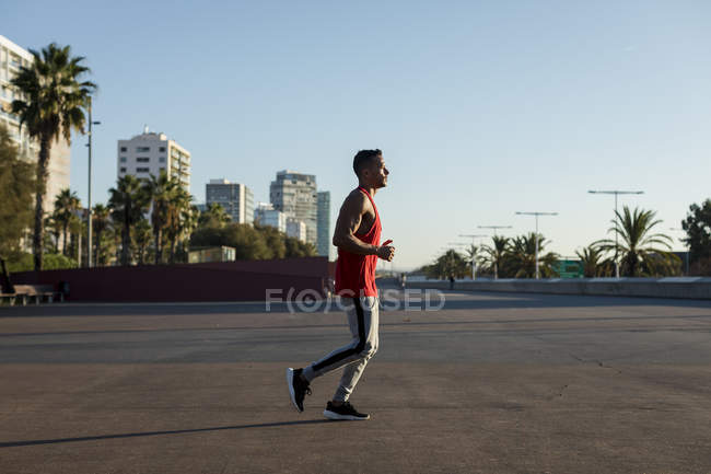 Muscular man jogging in the city — Stock Photo
