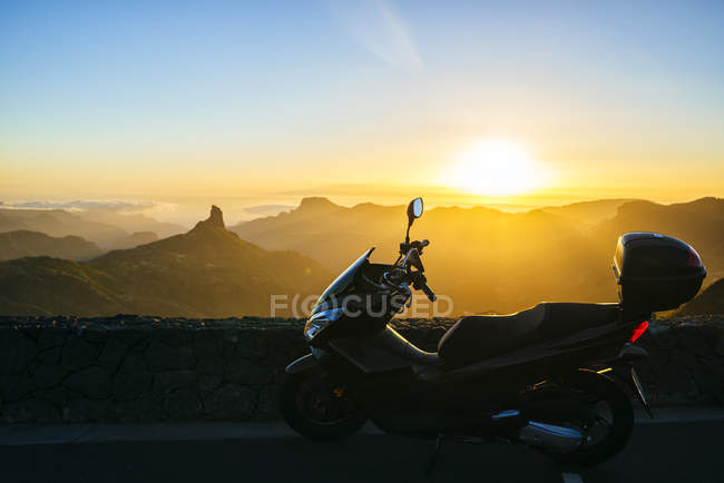 Spain, Canary Islands, Gran Canaria, parked motor scooter in front of mountainscape at sunset — Stock Photo