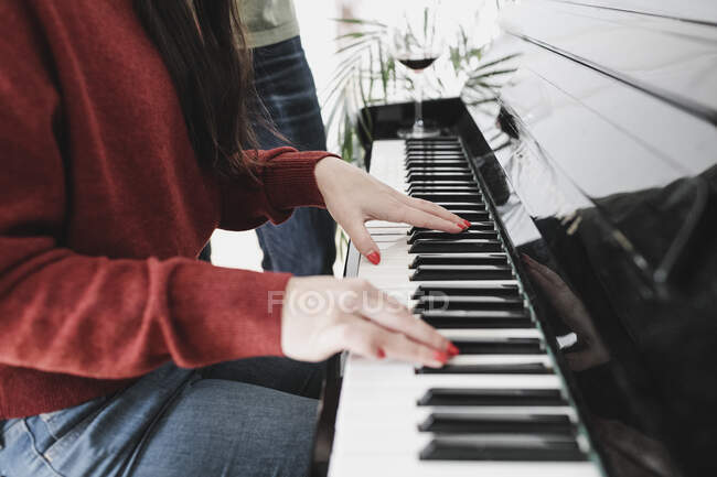 Mains d'une femme jouant du piano à la maison — Photo de stock