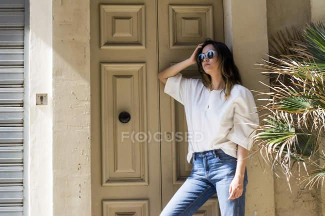 Портрет молодой женщины в солнцезащитных очках, склонившейся у входа в дом — стоковое фото
