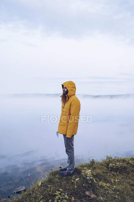 Швеція (Лапландія), чоловік з повною бородою, одягнений у жовте віконце, стоїть на краю води, дивлячись на відстань. — стокове фото