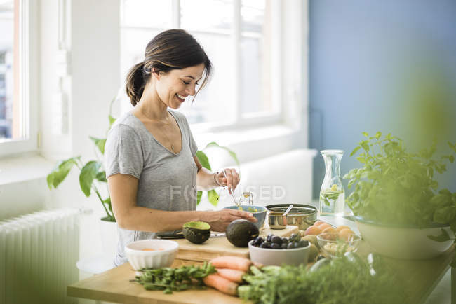 Woman preparing healthy food in her kitchen — Stock Photo