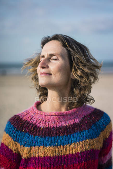 Donna matura godendo il vento sulla spiaggia, ritratto — Foto stock