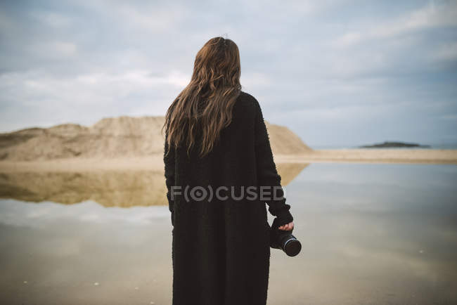 Back view of photographer dressed in black standing on the beach — Stock Photo