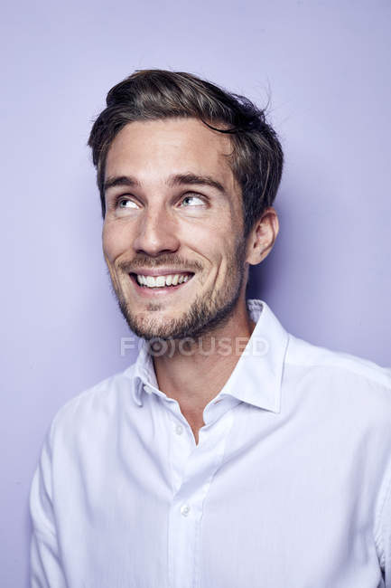 Portrait of laughing young man in front of purple background looking up — Stock Photo
